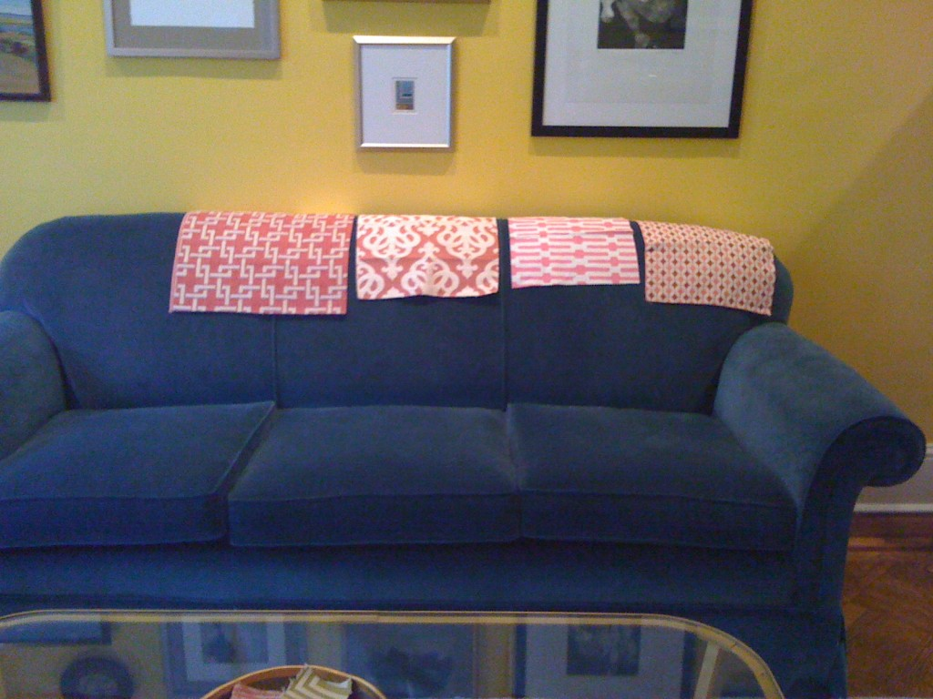Pink fabric swatches on blue sofa