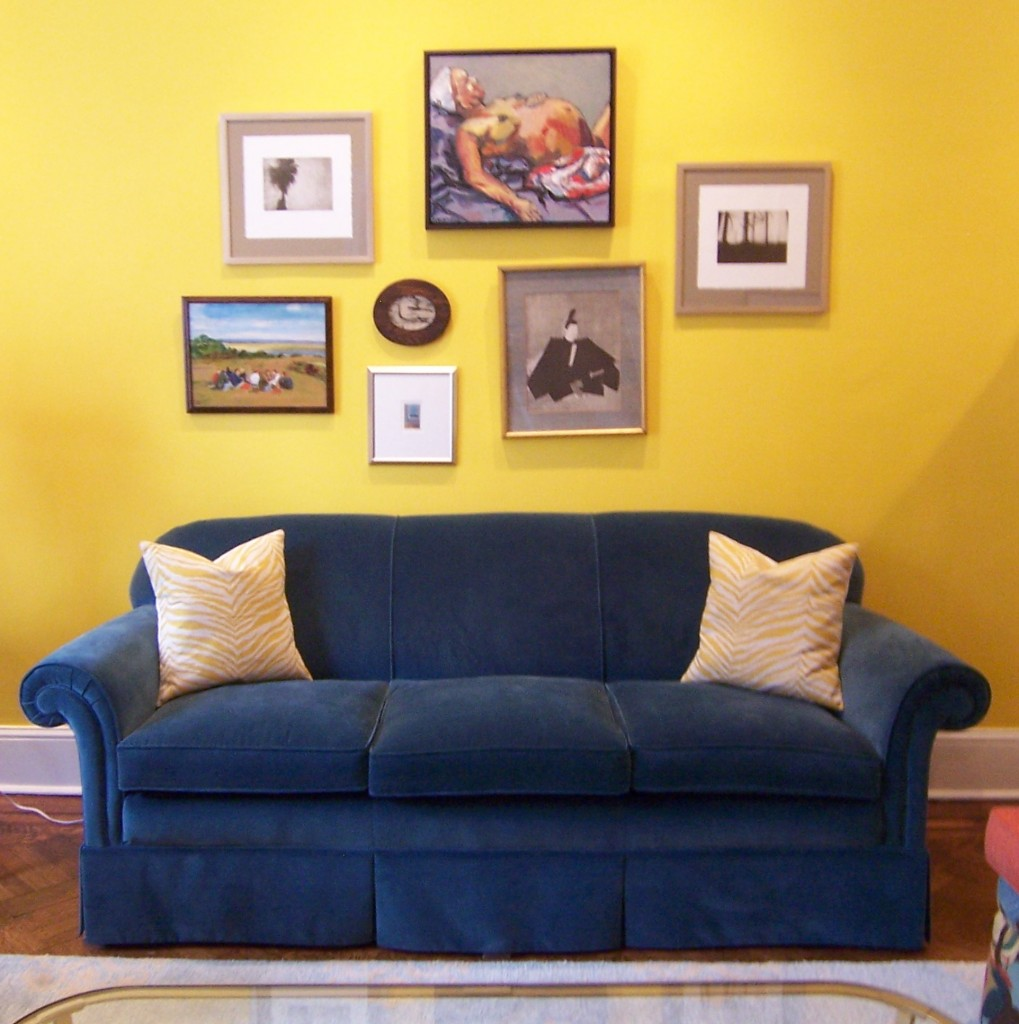 Blue sofa with yellow art wall