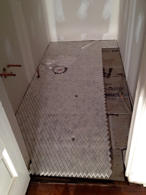 Carrara marble tile floor in powder room