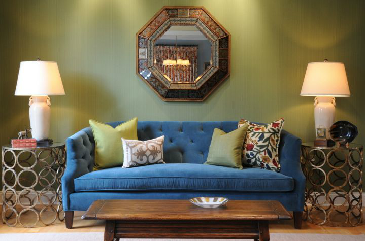 Green wallpapered living room with blue velvet sofa
