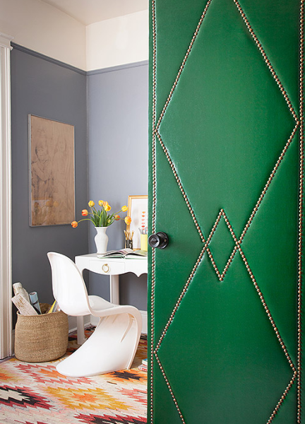 Green upholstered door into gray room