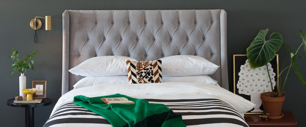 Gray headboard in gray bedroom with green accents