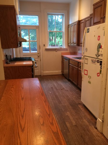 Galley kitchen with pink counters before renovation
