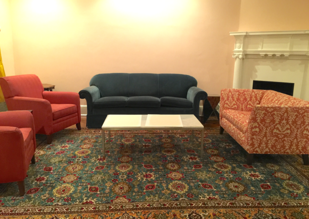 Pink walls with blue sofa and teal oriental rug