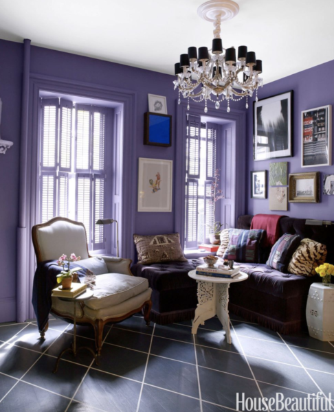 Small living room with purple walls and purple velvet banquette